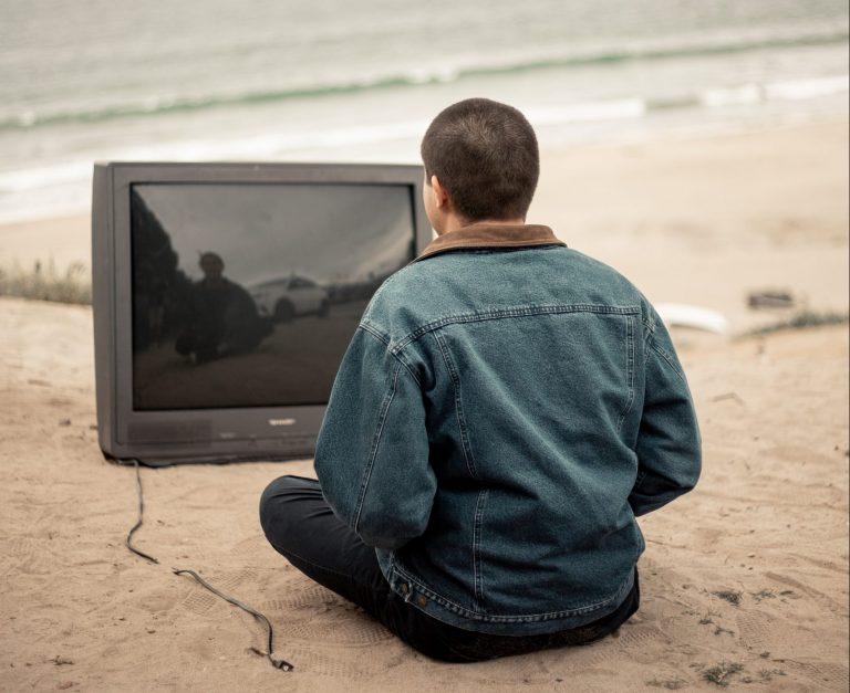 浜辺でテレビを見る男